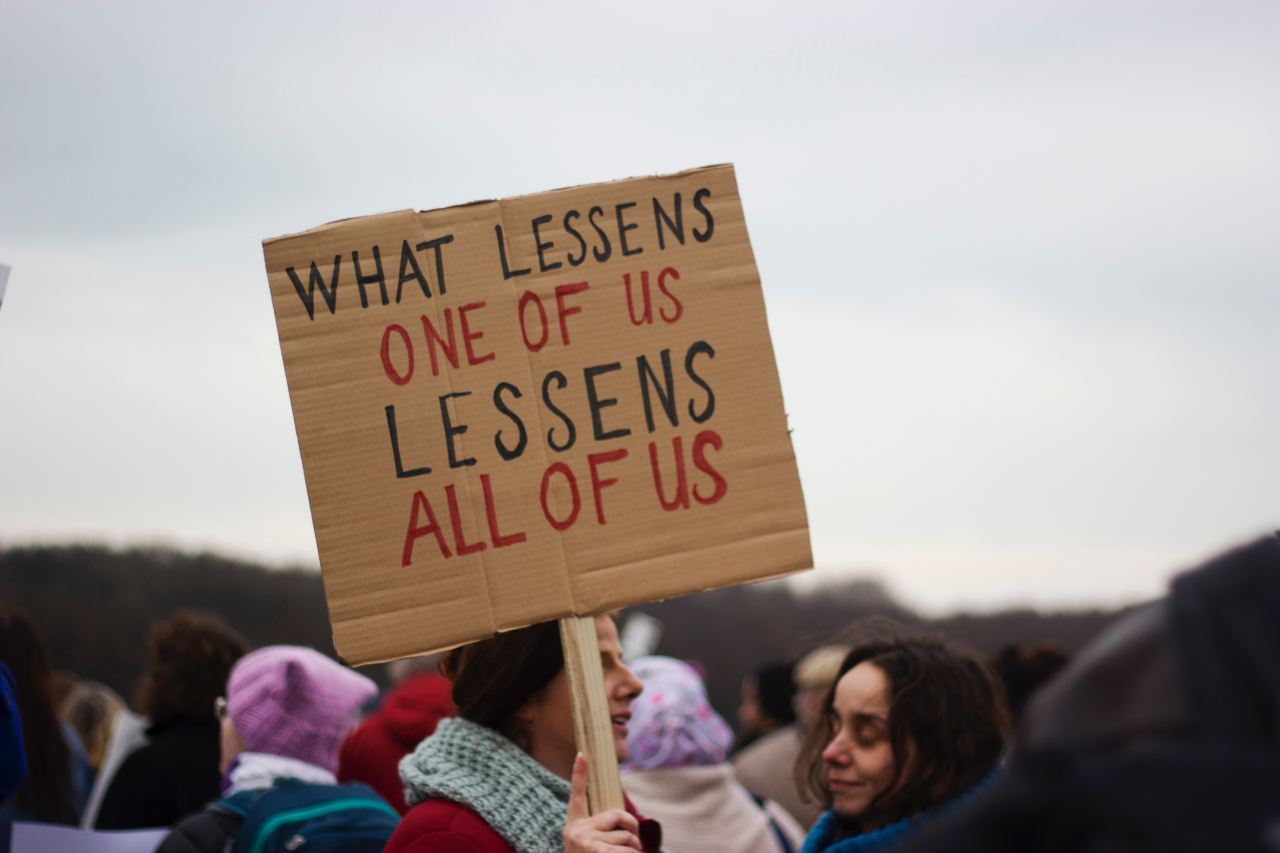 "Person holding sign with words: ""what lessens one of us lessens all of us"""