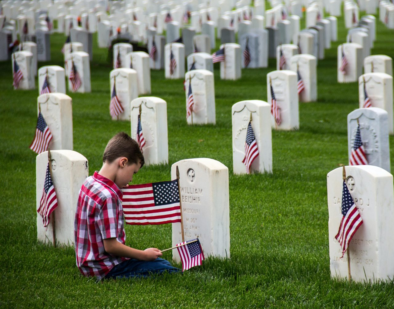 Boy kneels with American flag in front of rows of tombstones